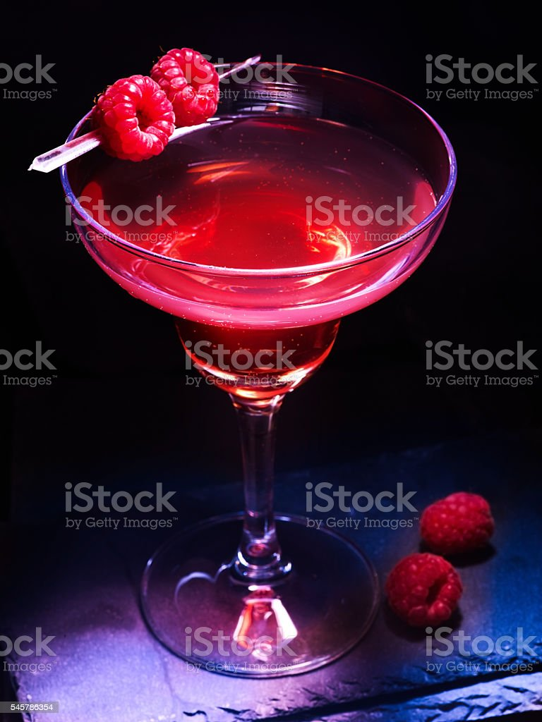 Raspberry martini cocktail on black background . stock photo
