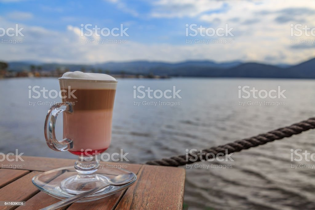 Raspberry mocha on the table with beach view stock photo