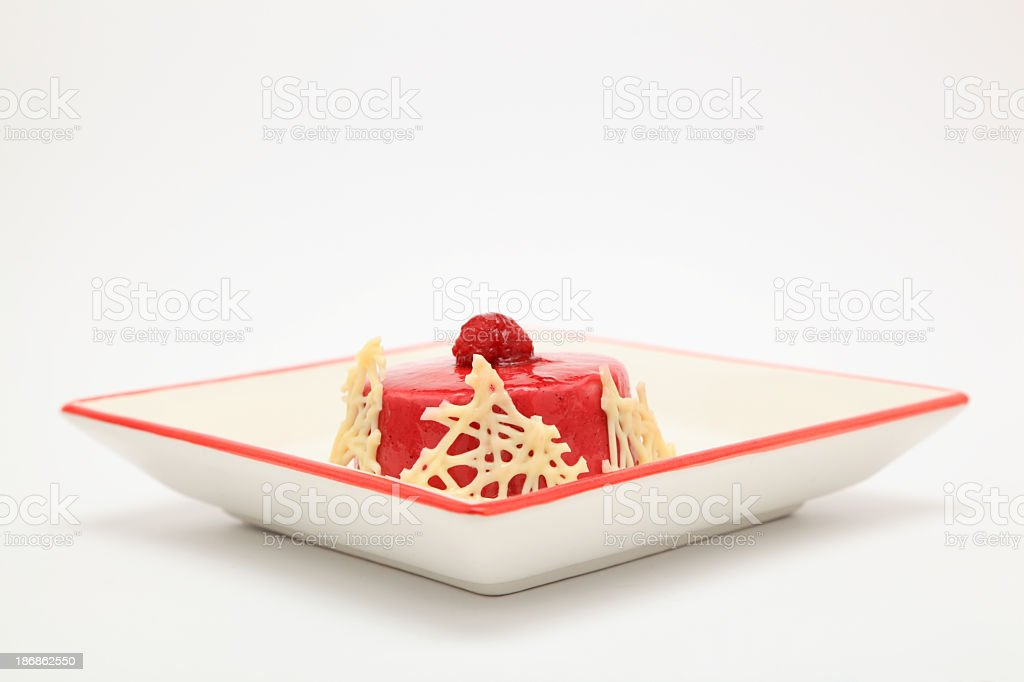 raspberry mousse dessert on square plate plain background stock photo