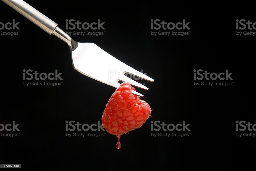 Raspberry on a fork stock photo