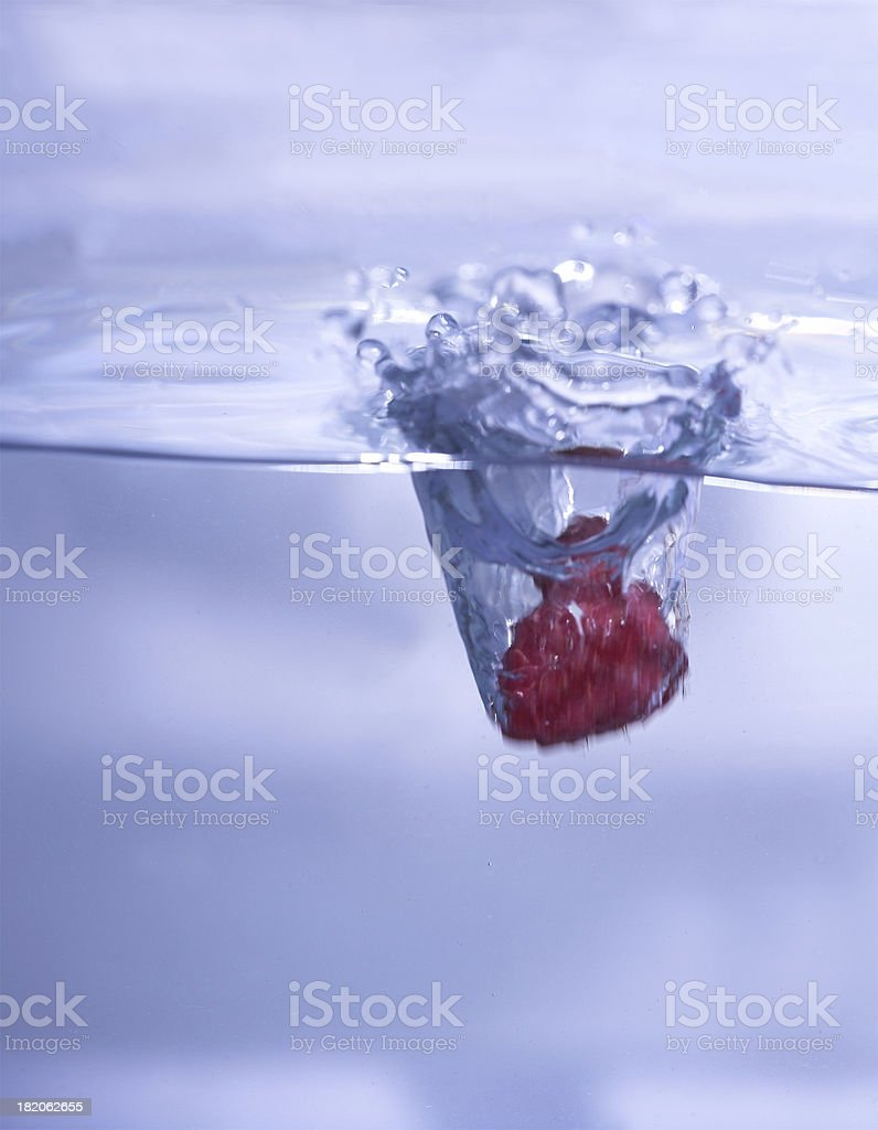 Raspberry plunging into water stock photo