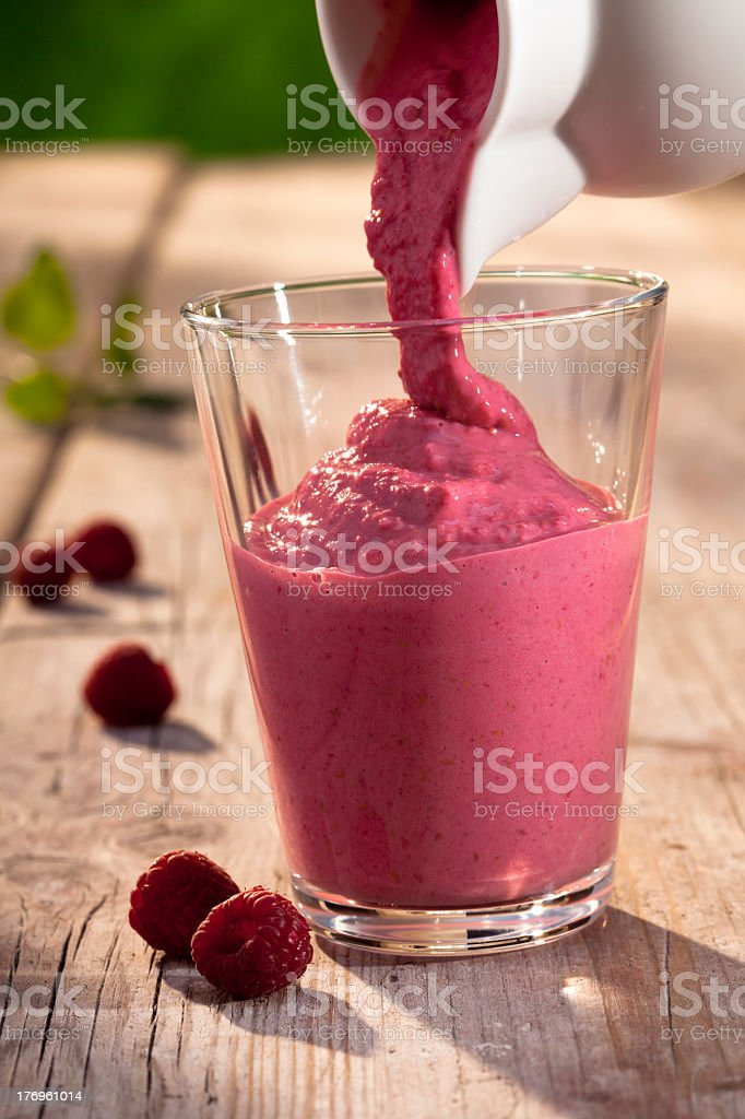 A raspberry smoothie being poured into a glass cup stock photo