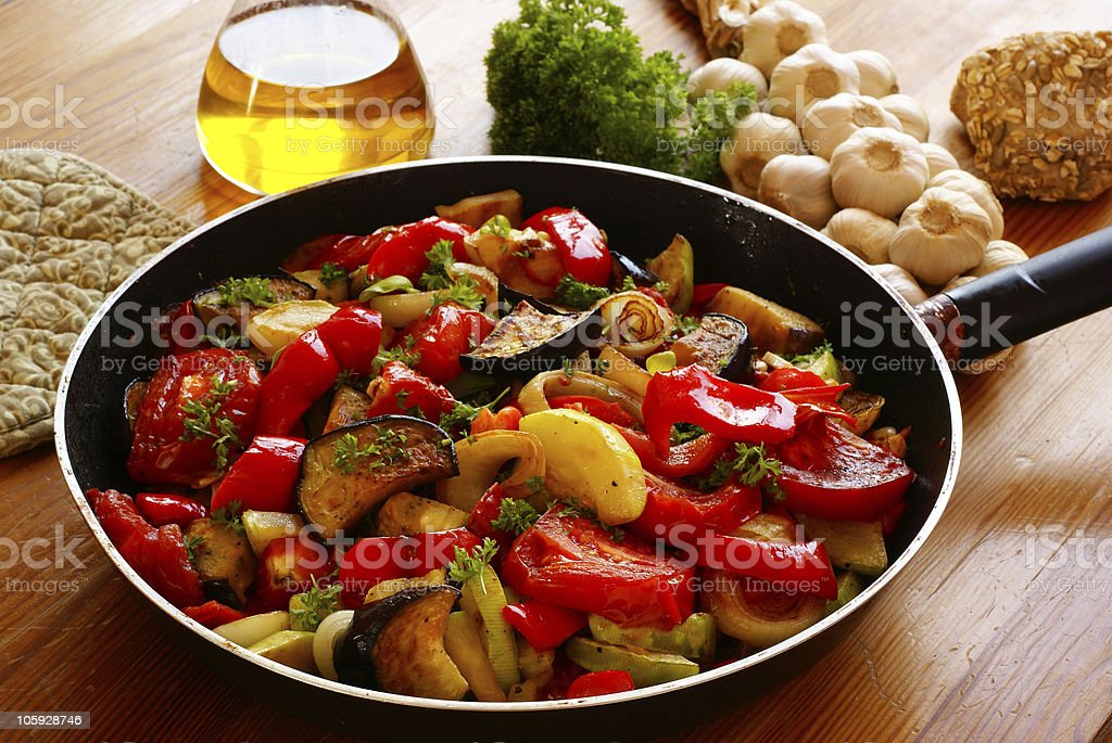 Ratatouille in a pan next to ingredients stock photo