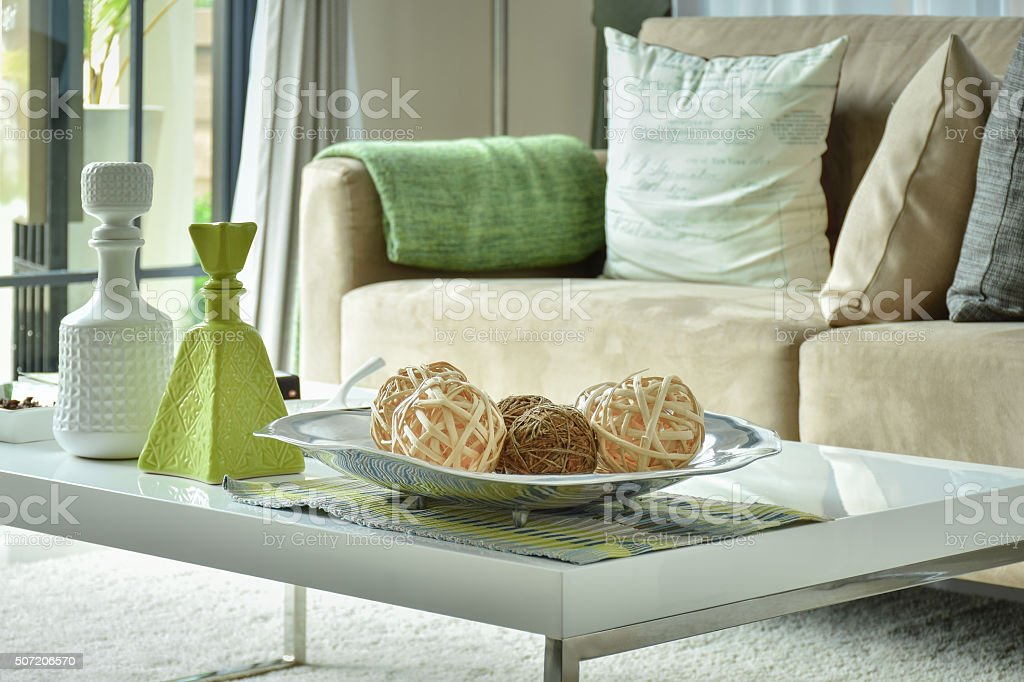 Ratten balls and vases on table with light brown sofa stock photo