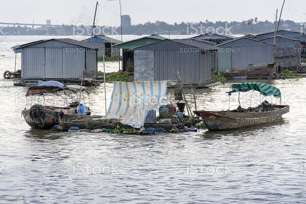 Ratty raft houses with fish cages floating on Mekong river stock photo