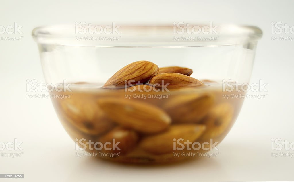 Raw almonds being activated in water stock photo