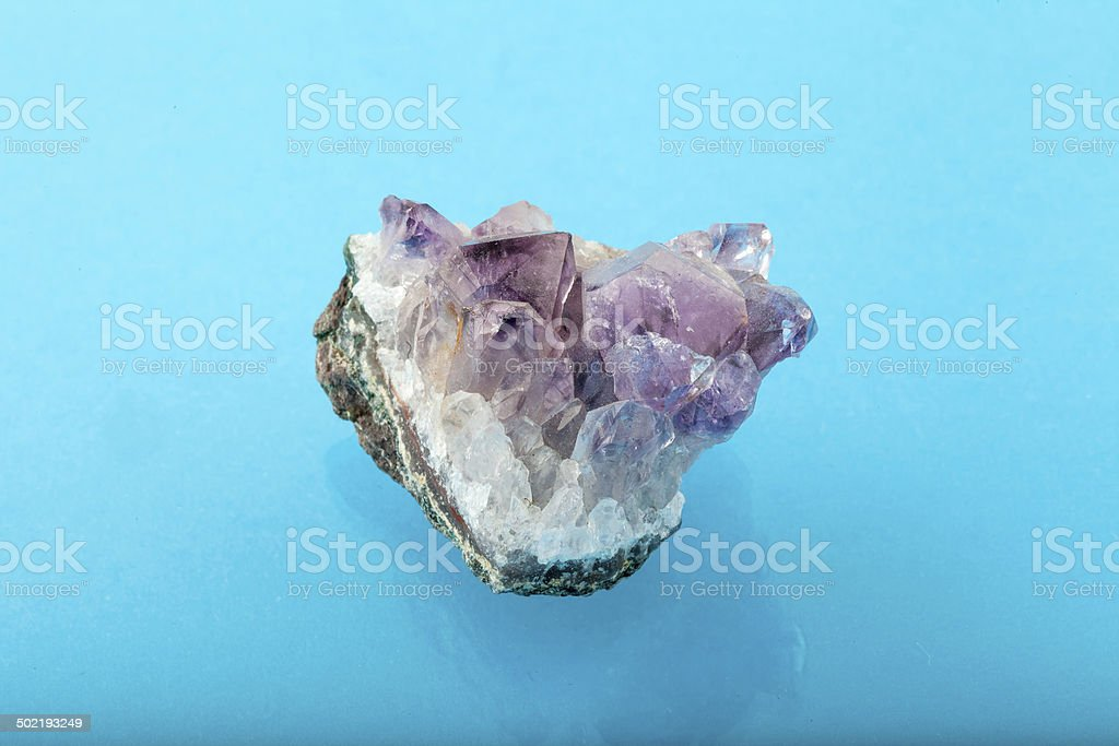 Raw amethyst rock with reflection on blue surface background stock photo