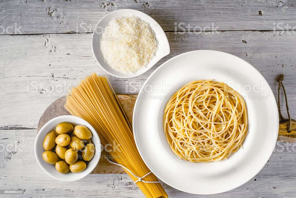 Raw and cooked spaghetti with olives and cheese top view stock photo