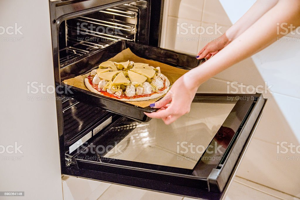 Raw and frozen pizza in the oven stock photo