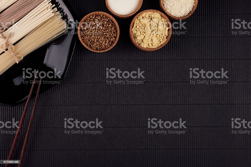 Raw asian noodles with ingredient in wooden bowls on black striped mat background with copy space. stock photo