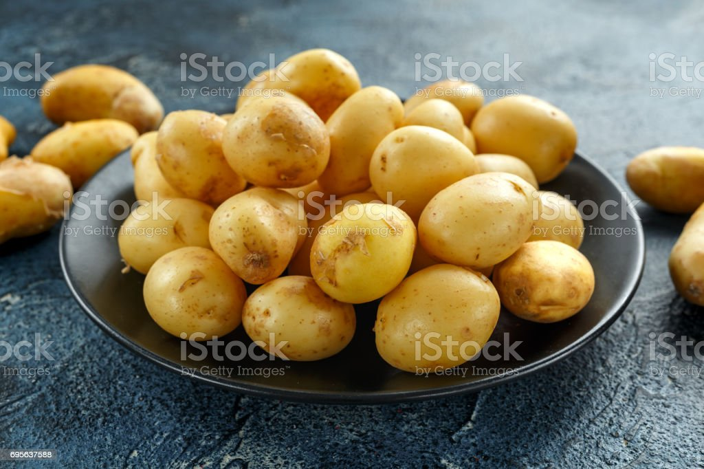 raw baby new potatoes in black plate stock photo