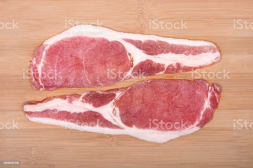 Raw bacon slices on a cutting board. stock photo