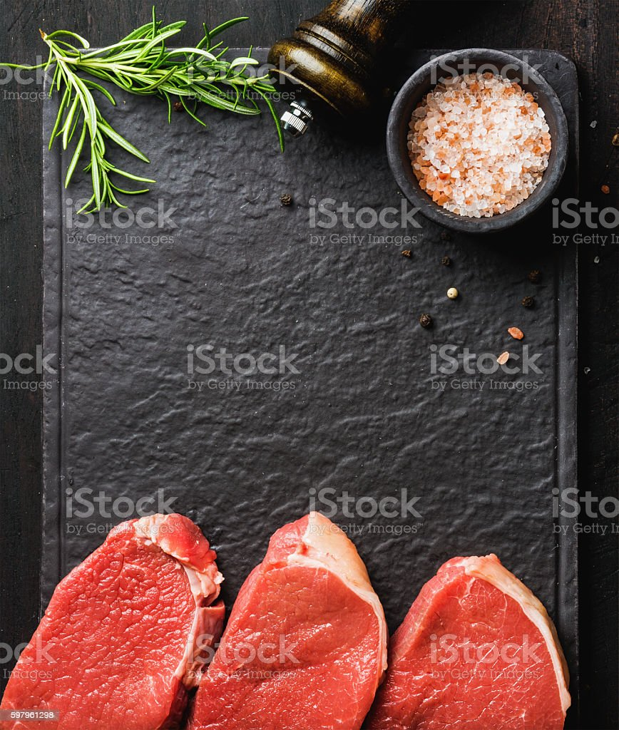 Raw beef Eye Round steaks with spices, rosemary. Copy space stock photo