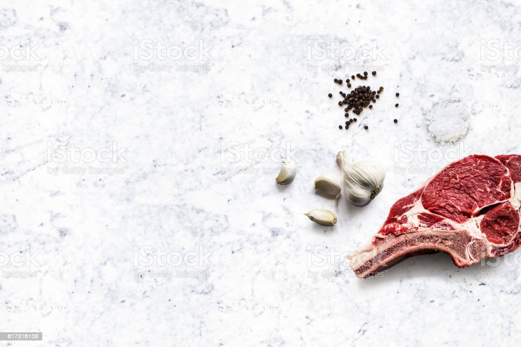 raw beef rib with some black pepper, sea salt and garlic on a white marble kitchen top stock photo