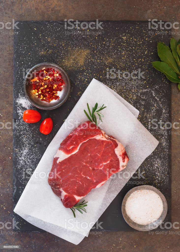 Raw beef sirloin steak on a parchment paper stock photo