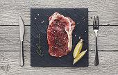 Raw beef steak on dark wooden table background, top view