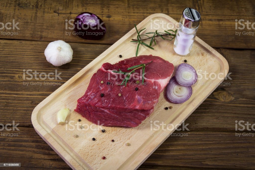 Raw beef steak on wooden table with rosemary stock photo
