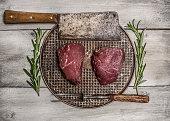 raw beef steak pan rosemary, meat cleaver fork rustic background