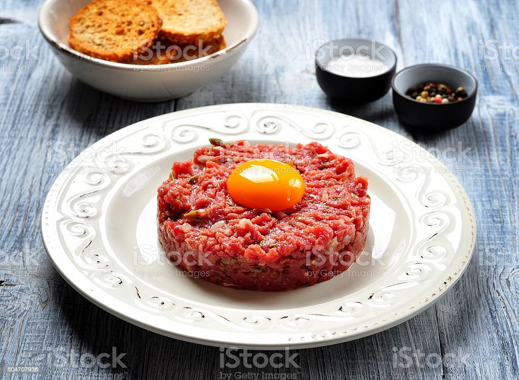 raw beef steak tartare with egg yolk, red onion stock photo