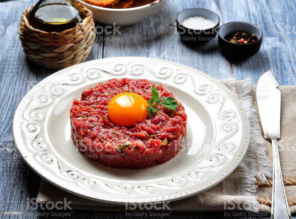 raw beef steak tartare with egg yolk, red onion, stock photo