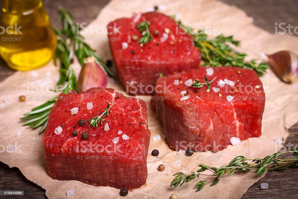 Raw beef steak with rosemary, thyme and garlic stock photo