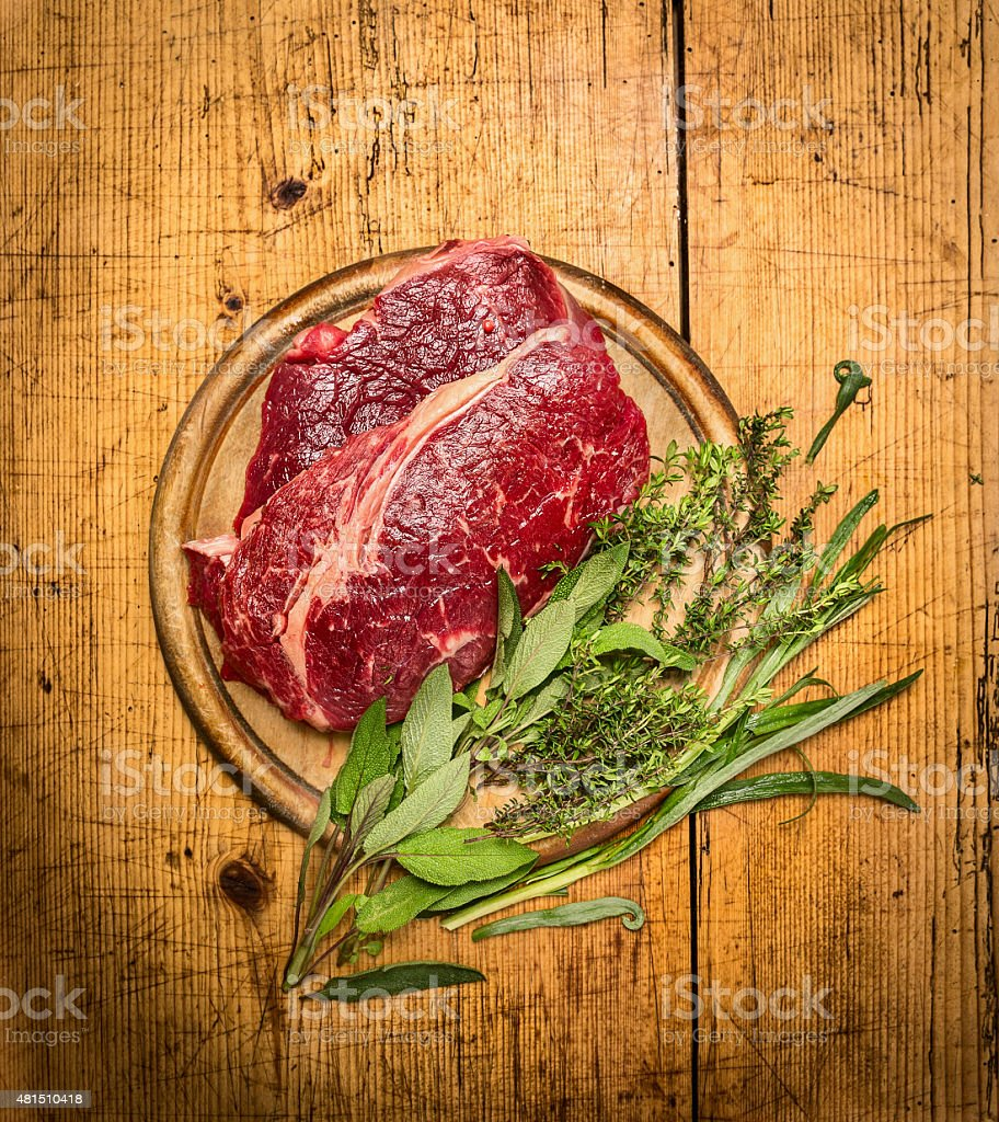 Raw beef steak with sage and tarragon herbs stock photo