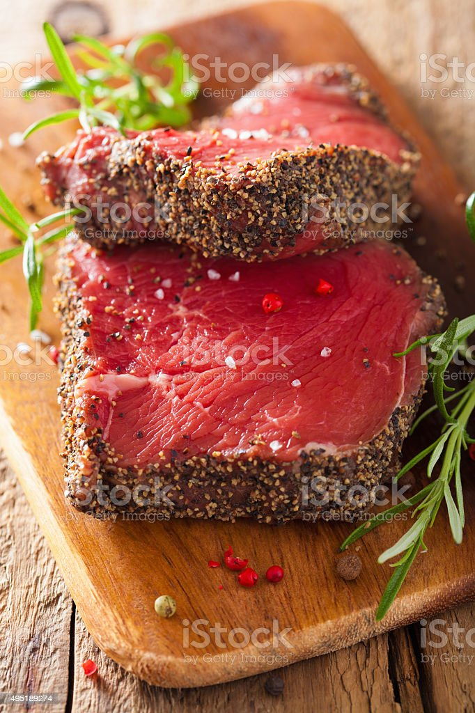raw beef steak with spices and rosemary on wooden background stock photo