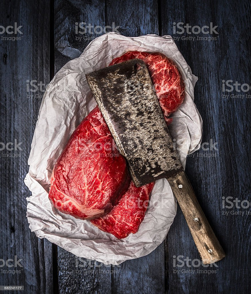 raw beef  with old meat cleaver on blue wooden background stock photo