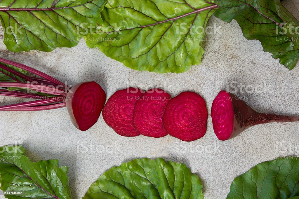 Raw beetroot sliced with leaves on rustic board. Top view. stock photo