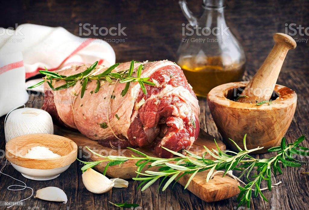 Raw boneless lamb leg with garlic and rosemary stock photo