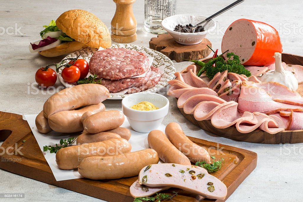 Raw burger with sausages, sliced ham and bacon stock photo