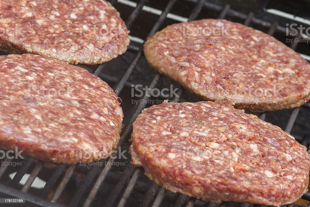 Raw  Burgers on a Barbecue royalty-free stock photo