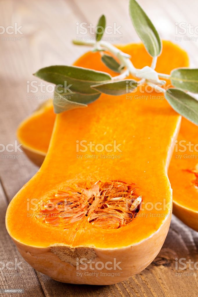 Raw butternut squash halved with sage stock photo
