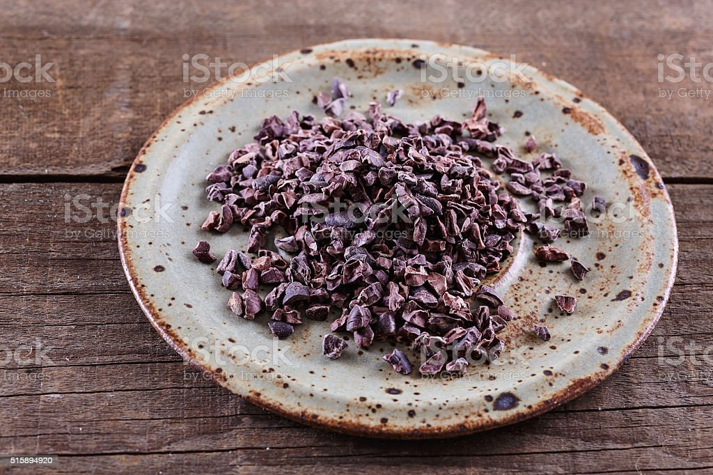 Raw Cacao Nibs over rustic wooden background stock photo