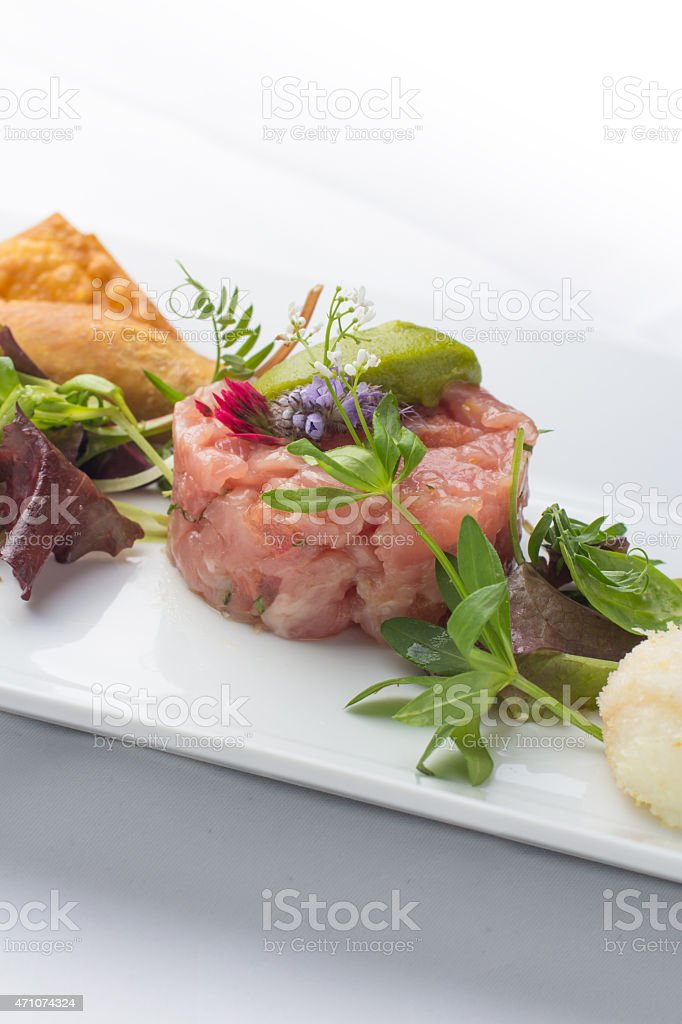 Raw calf beef tartare with variety of fresh herbs stock photo