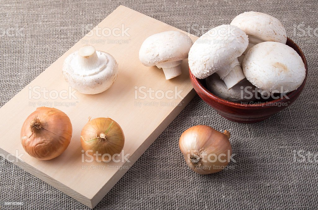 Raw champignon mushrooms and onions on the tabletop stock photo