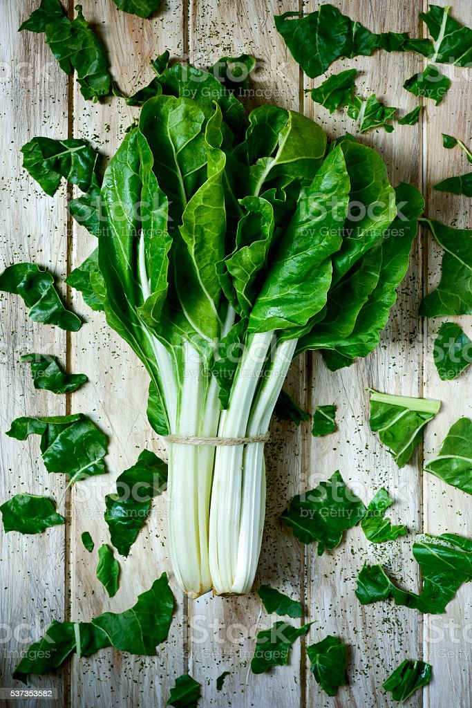 raw chard leaves on a rustic white table stock photo