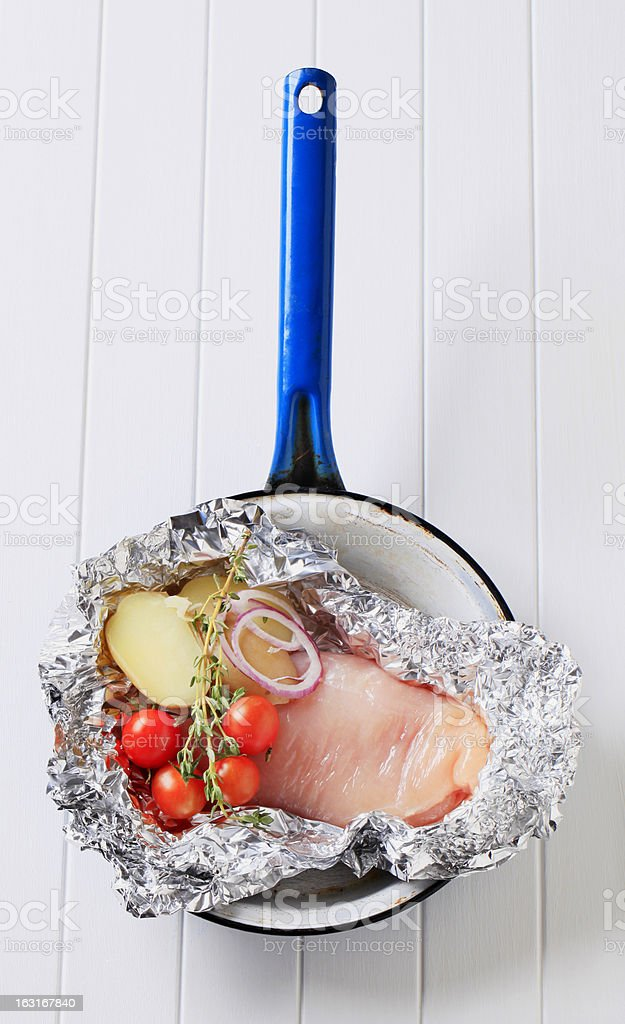 Raw chicken breast and vegetables in tinfoil royalty-free stock photo