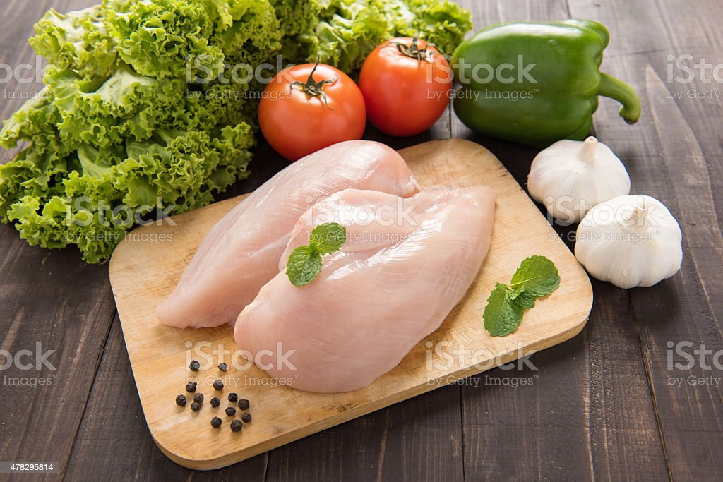 Raw chicken breast fillets and vegetable on wooden background. stock photo