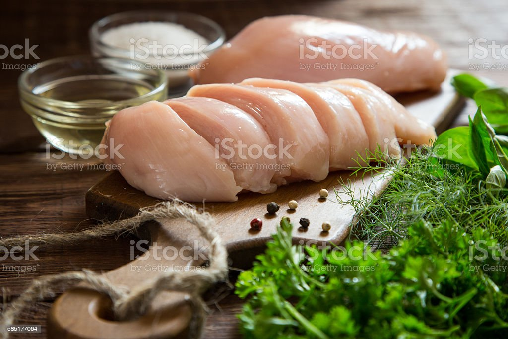 Raw chicken breast fillets and vegetable on wooden cutting board stock photo