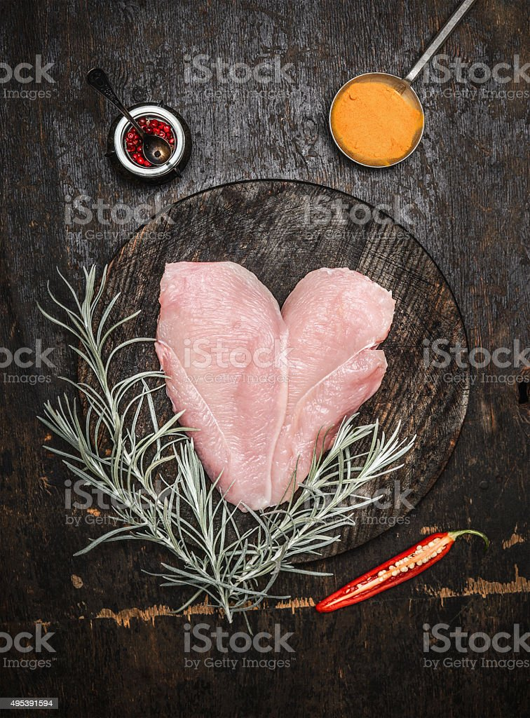Raw chicken breast in heart shape with herbs and spices stock photo