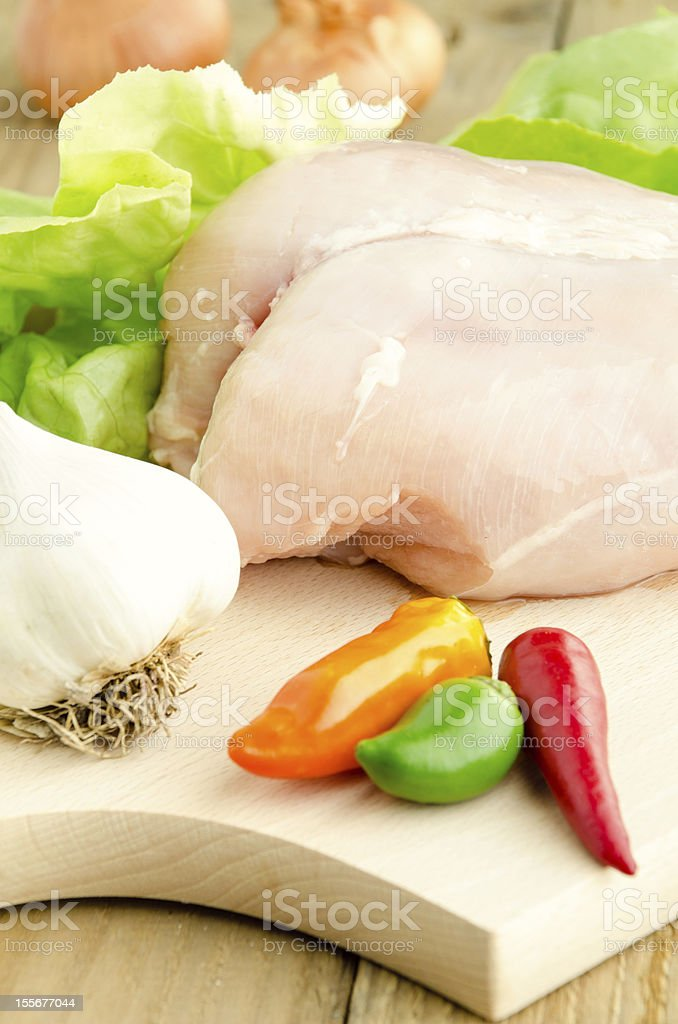 Raw chicken breasts on cutting board royalty-free stock photo