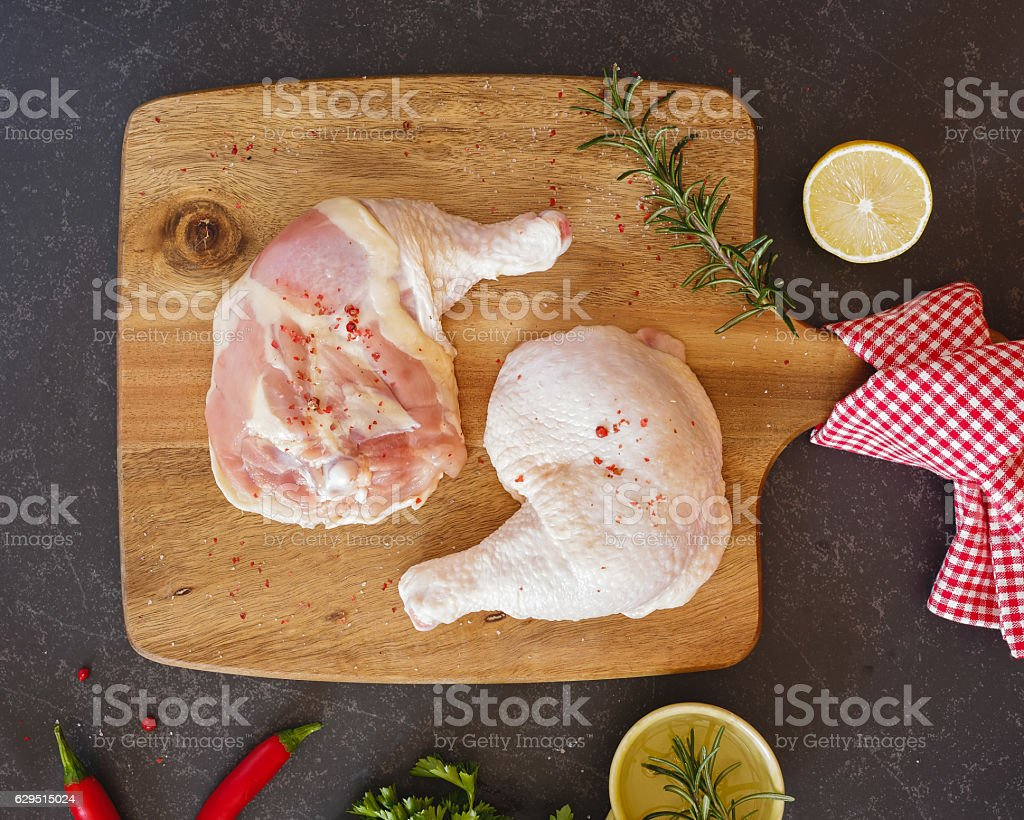 Raw chicken legs and thighs on a chopping board stock photo