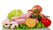 Raw chicken legs and vegetables for cooking isolated on white.