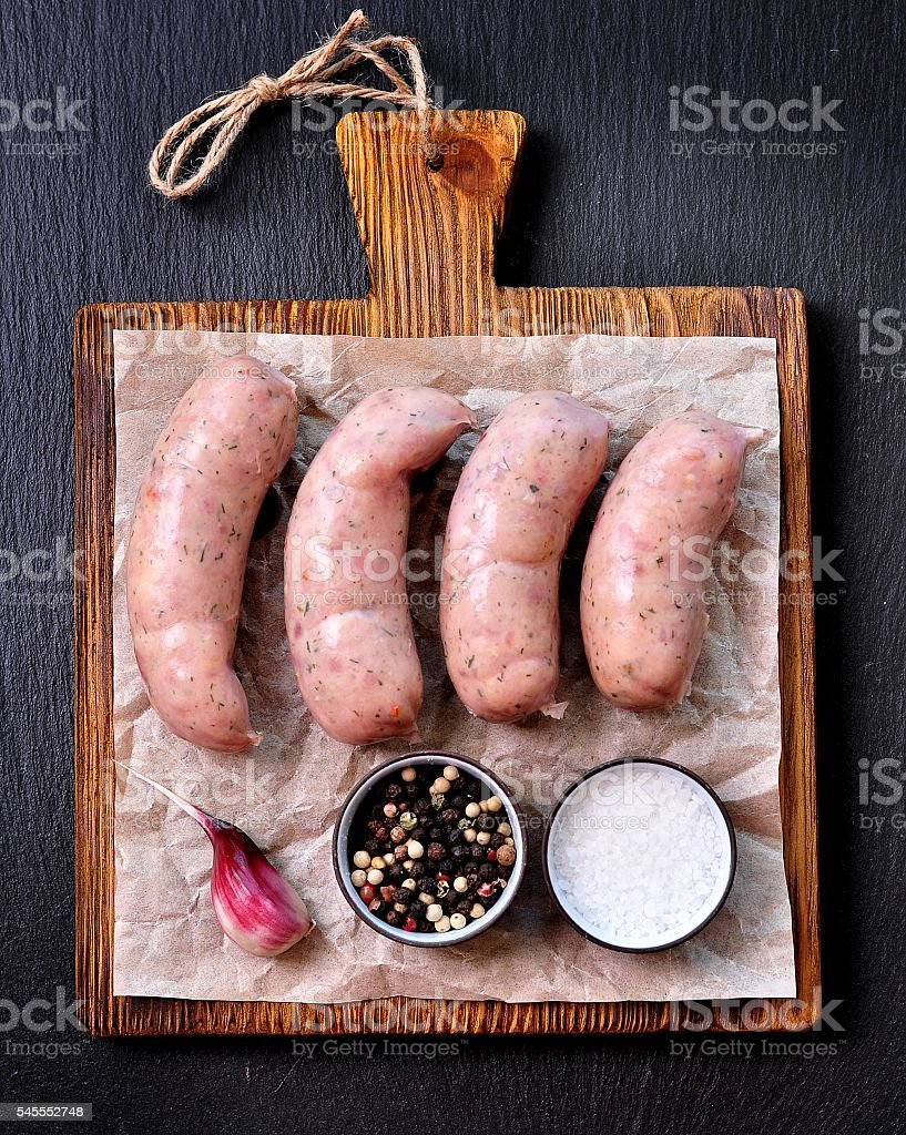 raw chicken sausages on a wooden cutting board stock photo