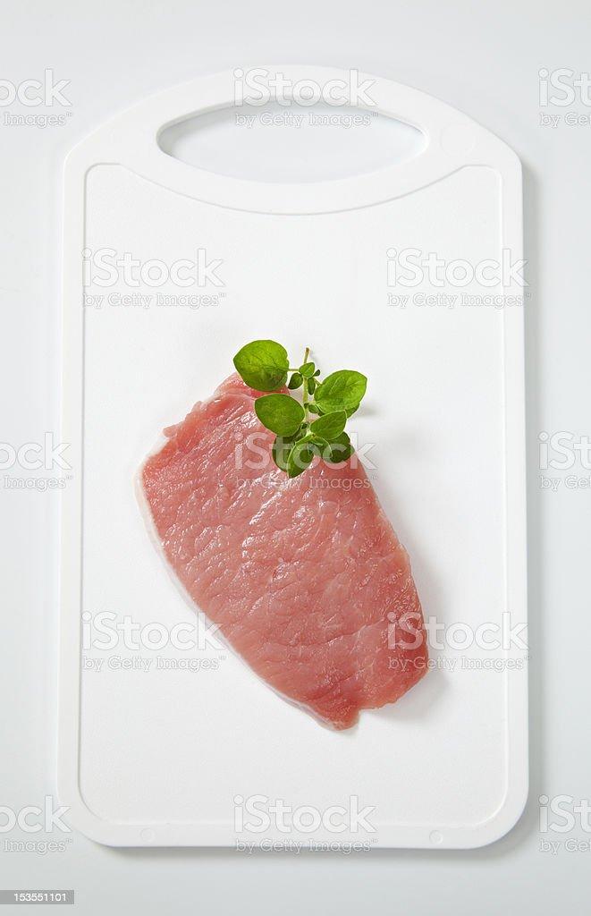 Raw chicken steak on a plastic salver, basil royalty-free stock photo