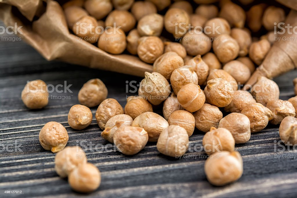 Raw chickpeas in paper bag stock photo