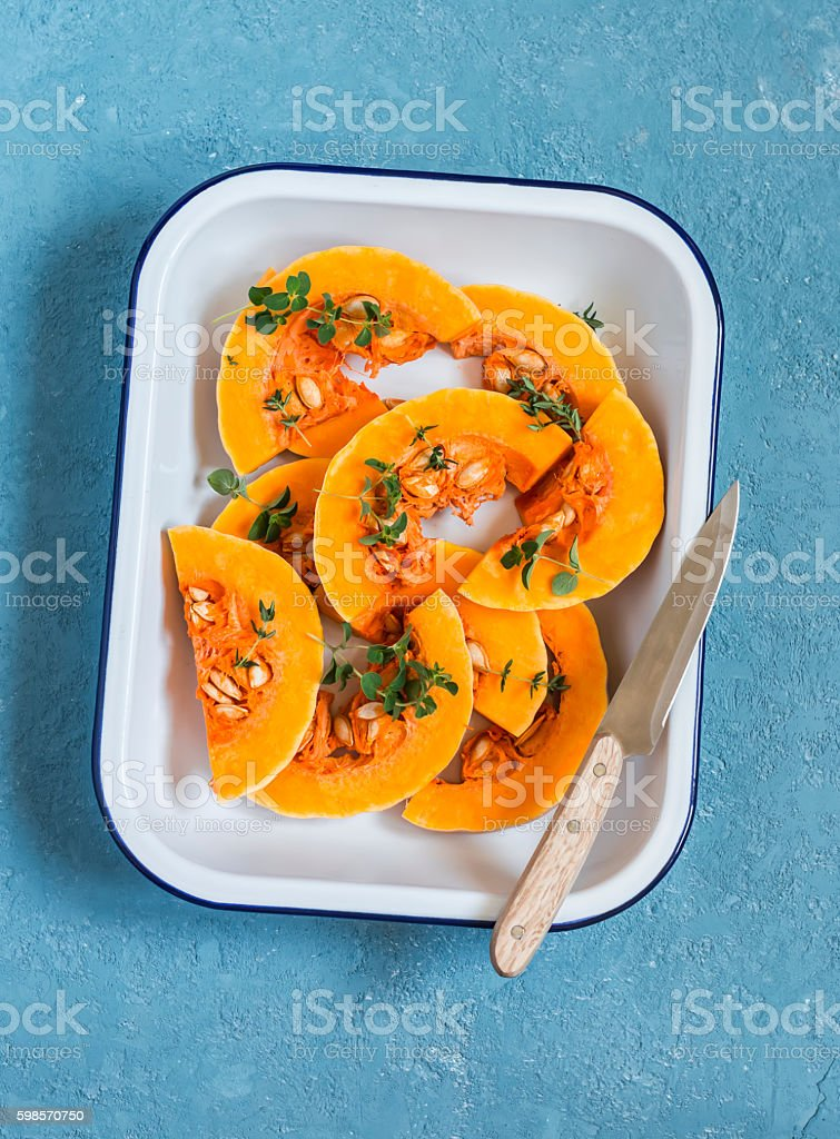 Raw chopped pumpkin in a baking dish on a blue background stock photo