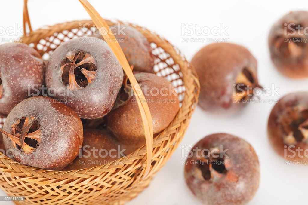 Raw common medlar fruits in the basket stock photo