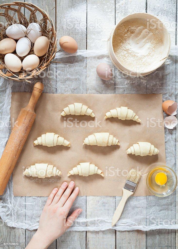 Raw croissants on parchment, preparation process. stock photo